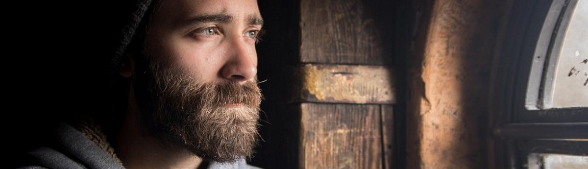 Sad man with a beard and beanie looking out a window